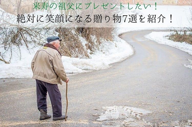 雪景色の道を歩く老人