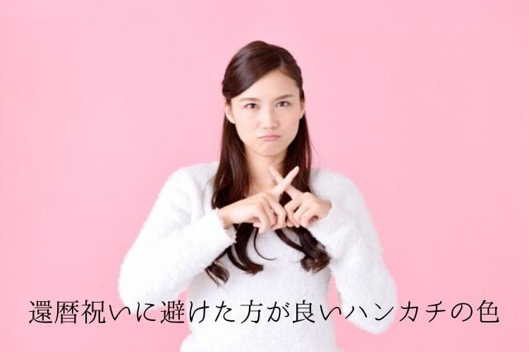 白い服を着た若い女性が指でバツサインをしている様子