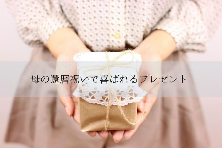 小さな手作り感のあるプレゼントボックスを両手の手の平にのせている女性