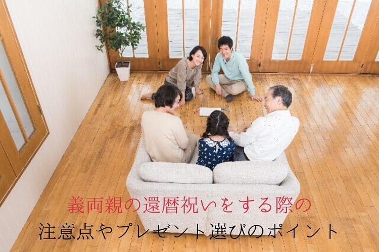 ソファに座った孫娘と祖父母、それを見守る夫婦