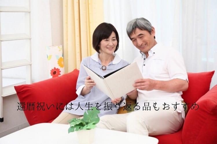 ソファに座りアルバムを笑顔で眺めるシニア夫婦