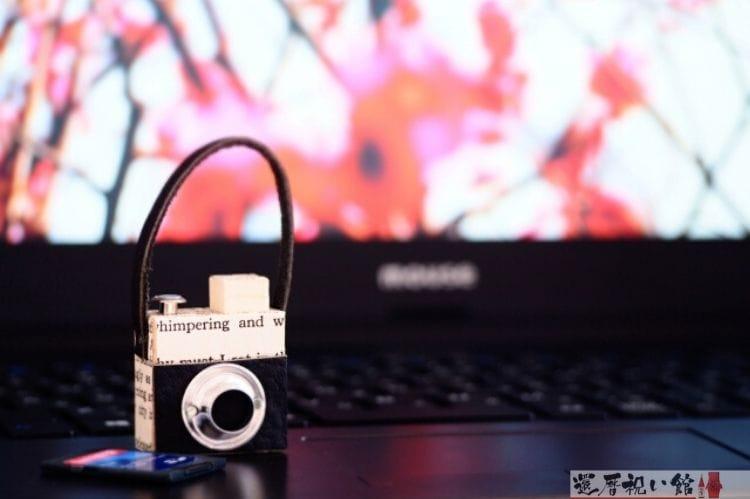ノートパソコンの上に置いてあるミニチュアのカメラ