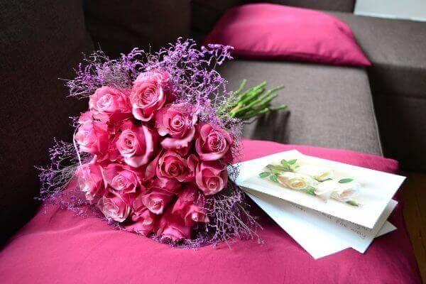 赤色系のバラの花束とクッション