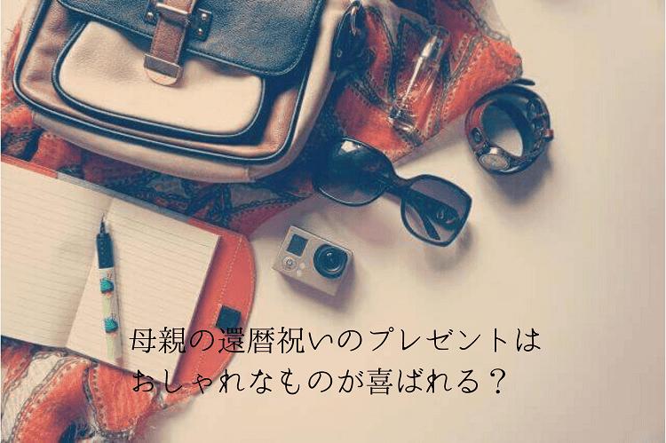 床に赤いスカーフやベージュのバッグ、サングラス、カメラ、時計、ノート、ペンなどが置かれている様子