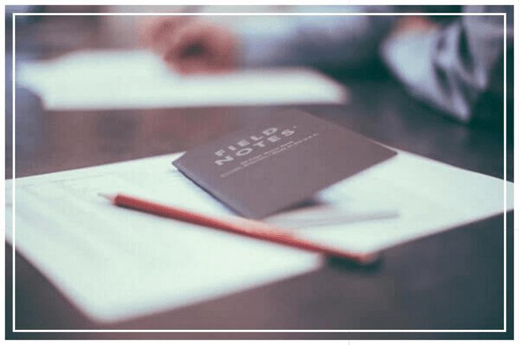 白い紙の上に置かれた鉛筆と小さな茶色のノート