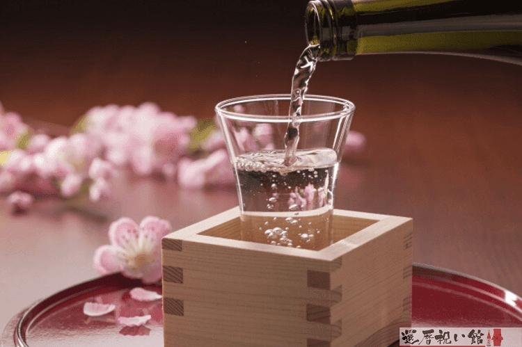 枡に入ったグラスに日本酒をそそぐ