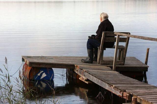 湖の前に座る老人