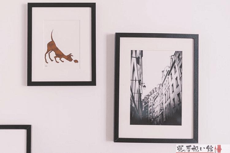 1枚は犬、もう1枚は街並みを描いた絵がフォトフレームに入れて壁に飾られている