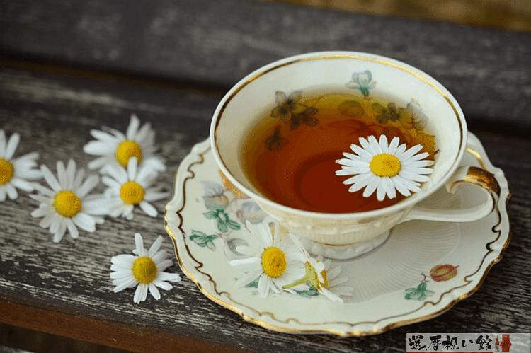 紅茶が入ったティーカップに白くて小さな花びらが1枚浮いている