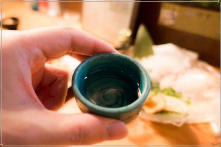 日本酒が入った緑の陶器のおちょこを手に持っている