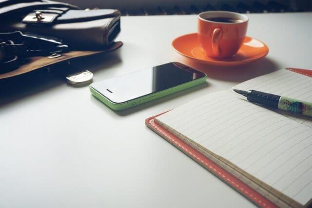 机に手帳とスマートフォンと珈琲と小物