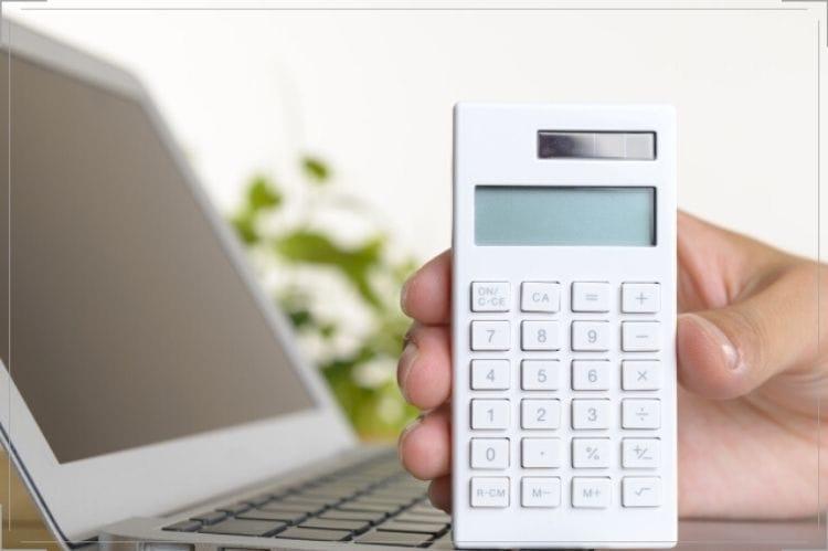 ノートパソコンの前で白い電卓を立てて持っている手