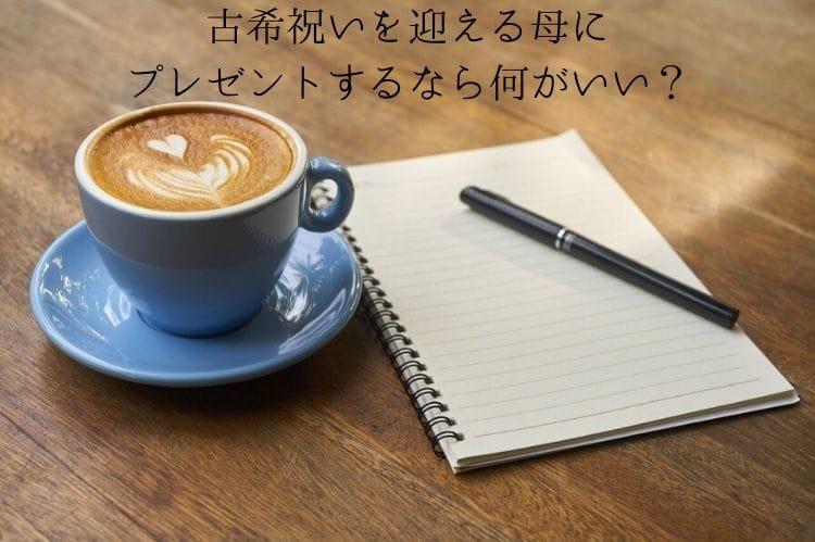 ノートとボールペンとラテアートが施されたカフェラテ