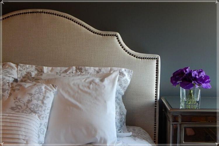 高級なベッドとそのサイドテーブルの上に置かれた紫の花