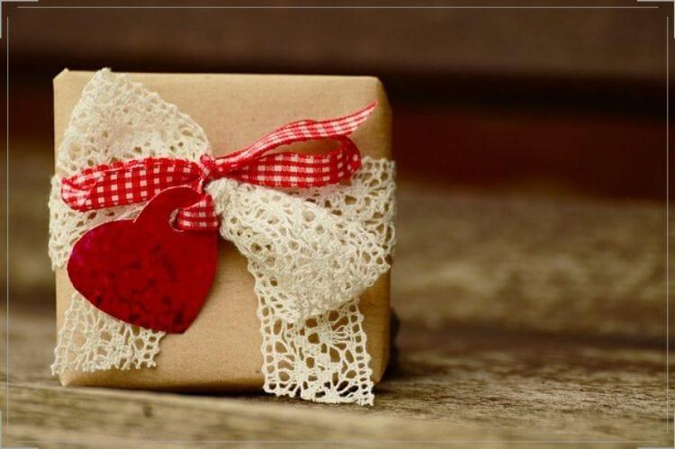 茶色の包みに赤のチェック柄リボンとレースが付いたプレゼントボックス