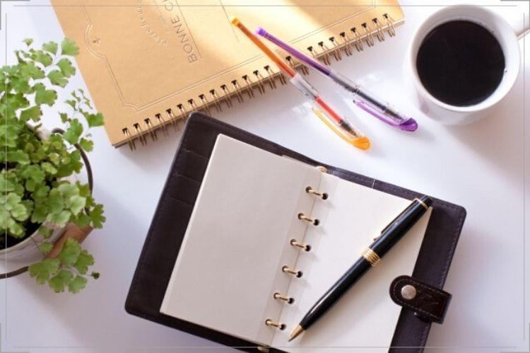 手帳、ボールペン、ノート、コーヒーが机に置いてある様子