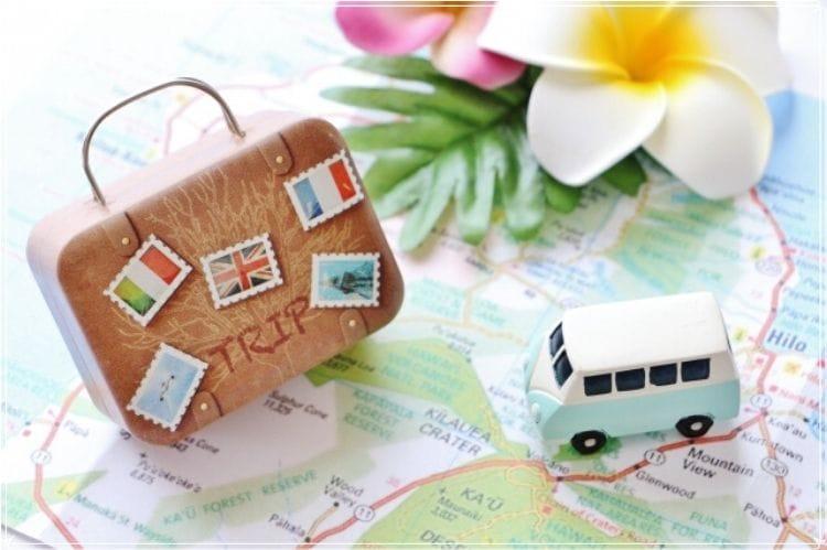 ミニチュアの旅行鞄と車が地図の上に置かれている
