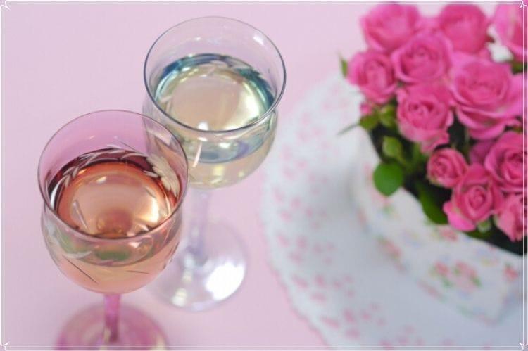 ピンクのバラの花束と白ワインもしくはシャンパンが入った2つのグラス