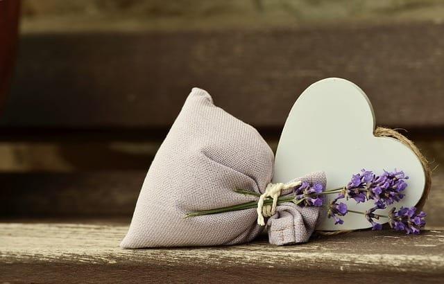 木製の白いハート型の雑貨と紫の花が入った袋が椅子の上に置かれている