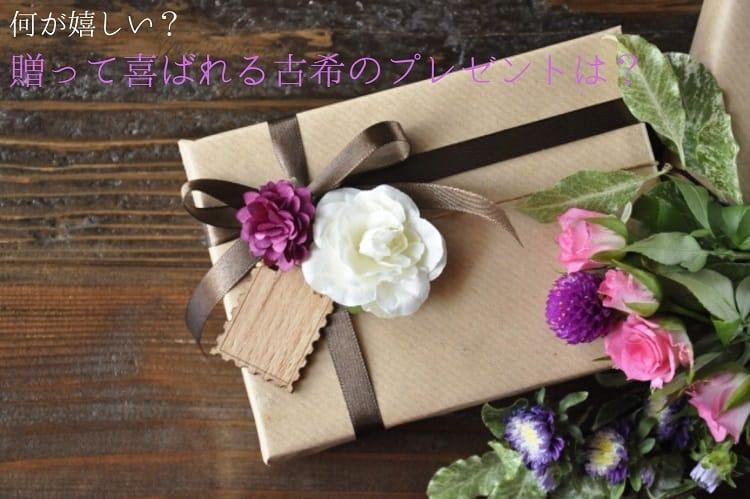 茶色の包みにこげ茶色のリボンと紫の花、メッセージカードが付いていて、その脇にピンクや紫の花が入った花束が添えられている