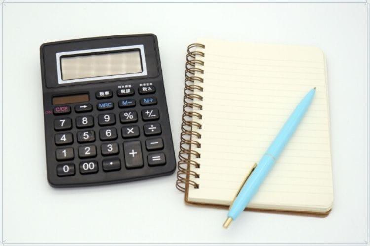 小さなメモノートと水色のボールペンと黒い電卓