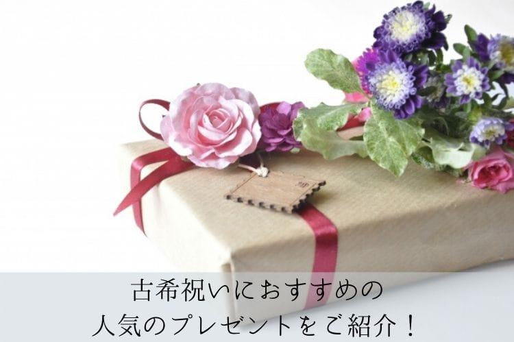茶色の包みに赤いリボンがついて、その上にピンクや紫の花が乗っているプレゼントボックス