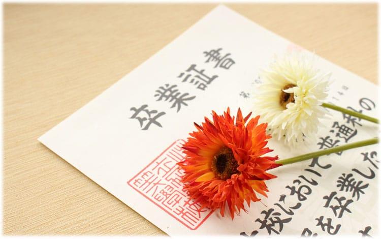 卒業証書とオレンジと白の花が一輪ずつ置いてある様子