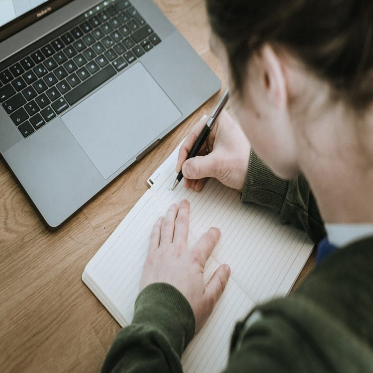 ノートパソコンの前でノートに文字を書く女性