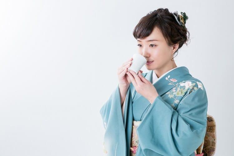 着物を着た女性が日本酒を飲む様子
