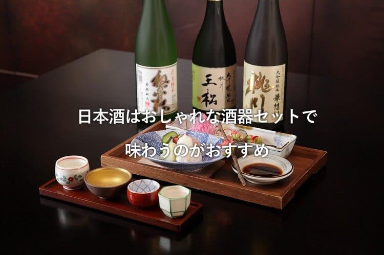 3本の日本酒の瓶と刺身の盛り合わせとおちょこ