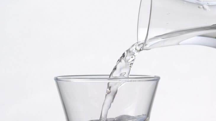 おしゃれなガラスのボトルから冷酒をつぐ