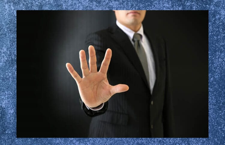 手を前に突き出してストップのサインをするビジネスマン