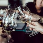 5人がシャンパンが入ったグラスで乾杯する様子