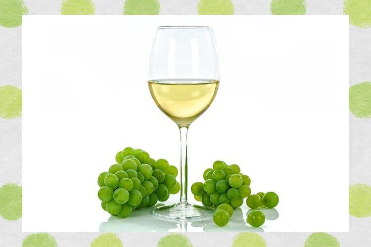 グラスに入った白ワインとぶどう