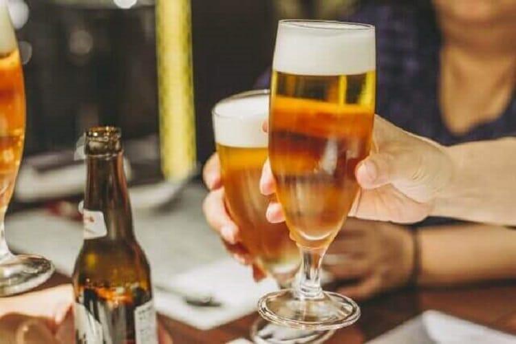 飲み屋でグラスに入ったビールを手に持つ