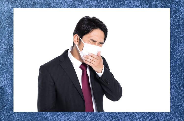 マスクをつけて口を押えて苦しそうにしているスーツ姿の男性