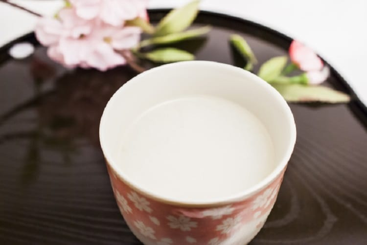 Amazake and a pink flower beside it in a pink colored teacup