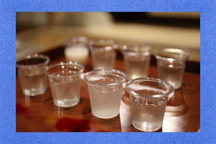 日本酒が入ったたくさんの小さな透明カップ