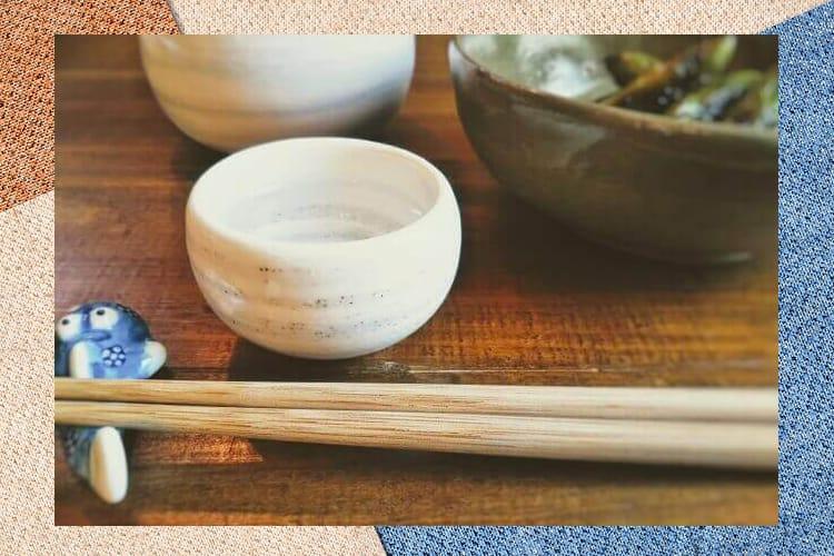 丸くて白いおちょことお惣菜、そして手前に置かれた箸