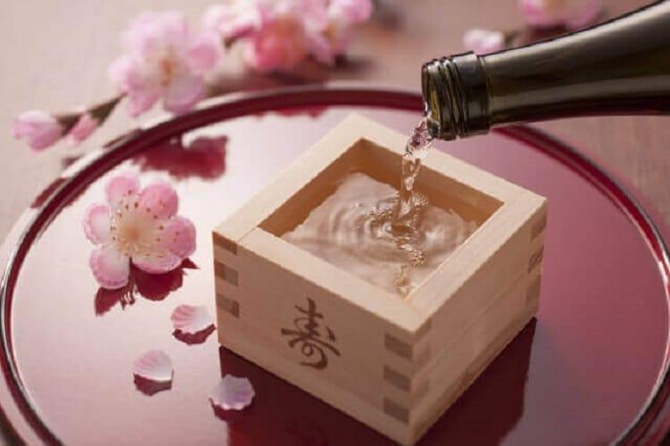 Versez le saké dans un bassin sur un plateau avec des fleurs de cerisier