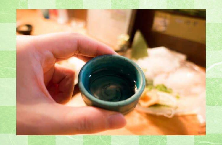 緑色のおちょこに日本酒が入っていて、それを手に掴んでいる様子
