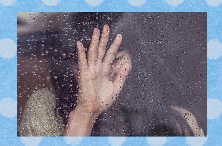 女性が家の中から雨でぬれた窓に手を触れて笑う様子