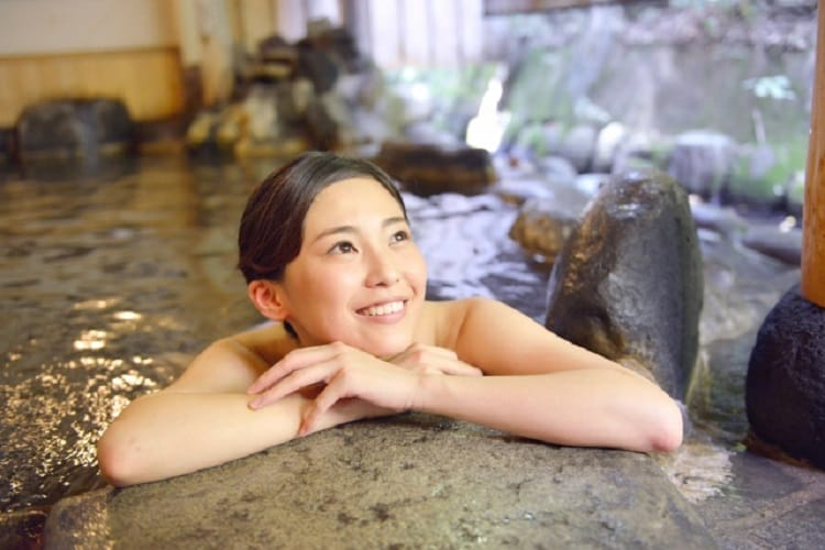 Woman relaxing in the open-air bath with a smile