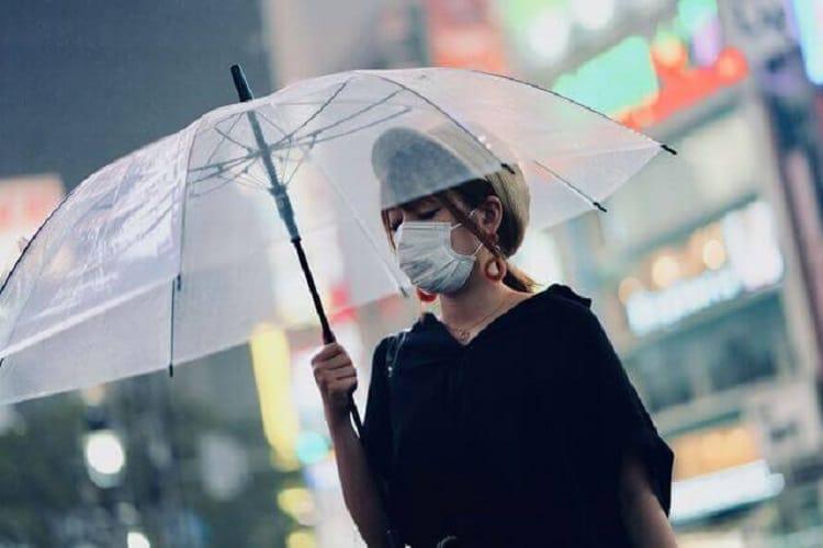 マスクをつけた女性が都会の中を傘をさして歩く様子
